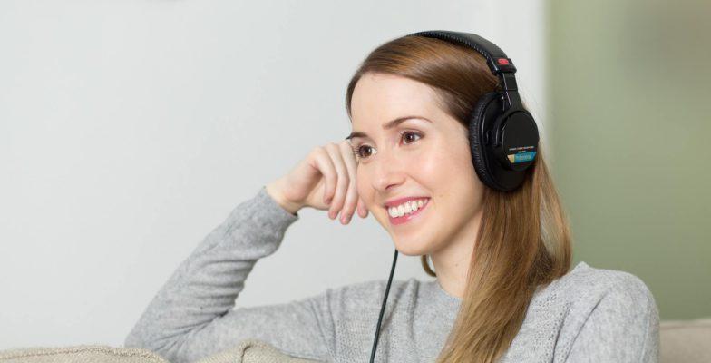 Frau mit Kopfhörern auf Sofa