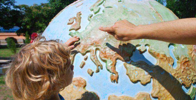 Kind erkundet eine Weltkugel. Thema: individuelles Lernen.